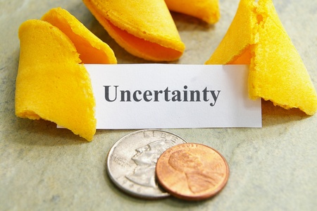 fortune cookie: Fortune cookie and coins with Uncertainty text Stock Photo