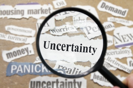 recession: News headlines and magnifying glass with Uncertainty text