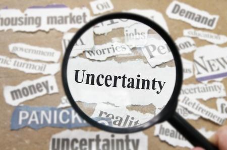 uncertain: Titulares de noticias y una lupa con el texto incertidumbre Foto de archivo