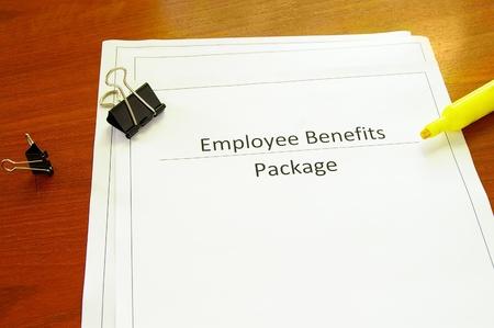empleados trabajando: Paquete de beneficios de empleado en un escritorio con miscel�neos suministros de oficina