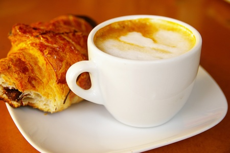 Cappuccino coffee and a chocolate croissant Imagens