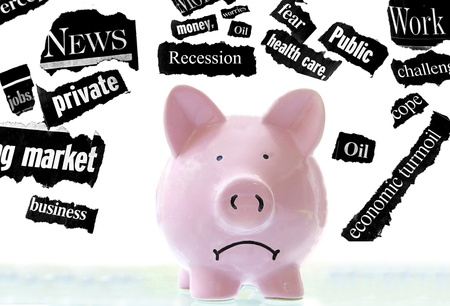 frowning pink piggy bank with bad economic news headlines photo