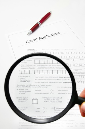 business credit application: a blank credit application and magnifying glass