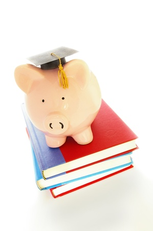 piggy bank and graduation cap on books - student debt concept photo
