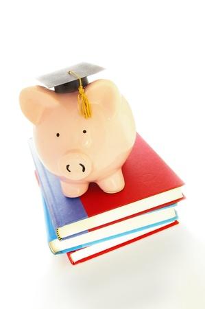 piggy bank and graduation cap on books - student debt concept