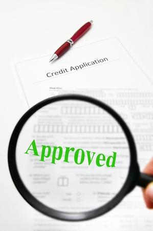 een kredietaanvraag en vergrootglas met goedgekeurde tekst Stockfoto