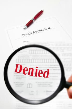 credit score: a blank credit application and magnifying glass with Denied text