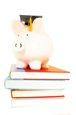 cost of education: piggy bank on book pile - student debt concept