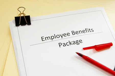 an employee benefits package and red pen photo