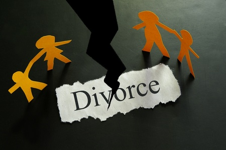 divorce: torn piece of paper with divorce text and paper family figures