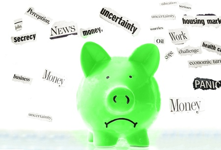 frowning pink piggy bank with bad economic news headlines Stock Photo - 11717347