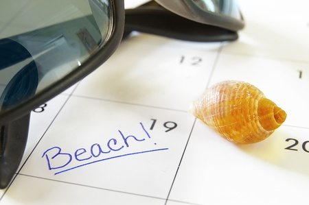 closeup of a calendar with Beach text with seashells and sunglasses photo