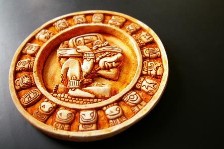 A carved Mayan calendar on dark background photo