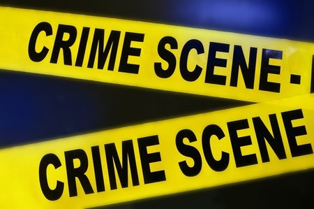 scene of a crime: yellow crime scene tape on dark background
