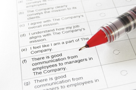 job satisfaction: closeup of a blank employment survey with red pen