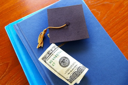 cash and small graduation cap on a pile of books photo
