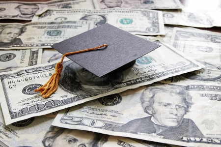 college graduate: mini college graduation cap on cash