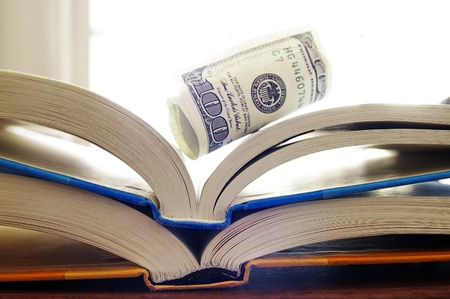 rolled up cash on open books Stock Photo - 12463151