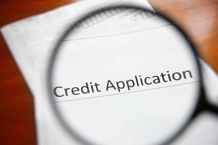 credit score: magnifying glass and a credit application form