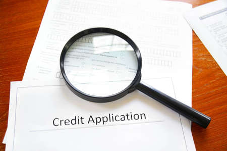 business credit application: magnifying glass on a blank credit application