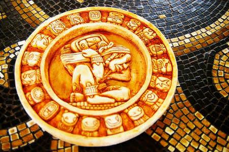 Carved stone Mayan calendar on tile background photo
