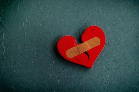 赤の傷ついた心を青色に織り目加工の包帯 写真素材