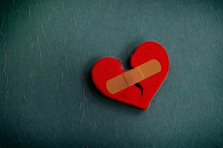 red broken heart with a bandage, on textured blue photo