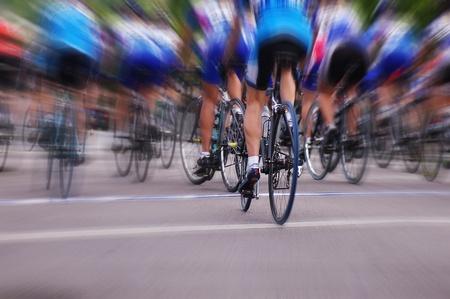 jinete: Borrosa corredores de bicicletas profesionales en una carrera de ruta