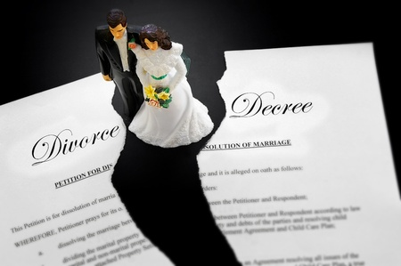 decree: cake-topper wedding couple on a torn divorce document Stock Photo