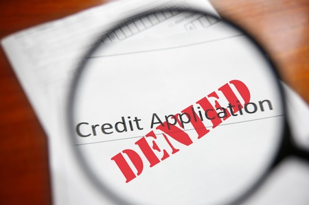 bad business: magnifying glass and a Denied credit application form