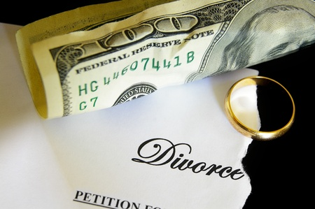 divorce court: torn divorce decree and cash, with wedding ring