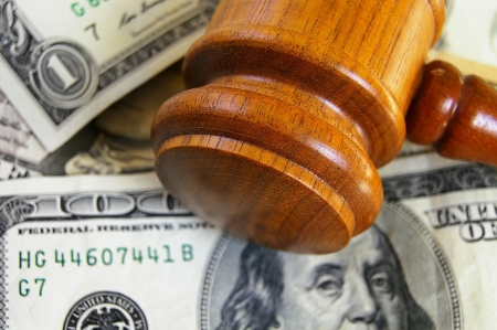 judgements: closeup of a gavel on cash, from above