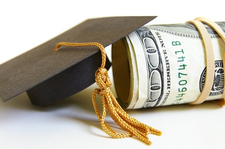 education loan: graduation cap and cash roll, closeup