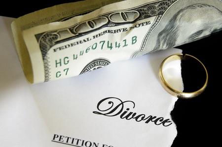 torn divorce decree and cash, with broken wedding ring photo