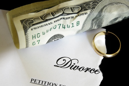 divorce court: torn divorce decree and cash, with broken wedding ring Stock Photo