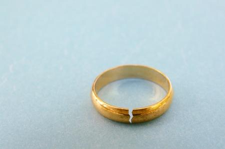 close-up van een gouden trouwring met een scheur in het concept van scheiding Stockfoto