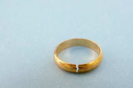 broken relationship: closeup of a gold wedding ring with a crack in it   divorce concept