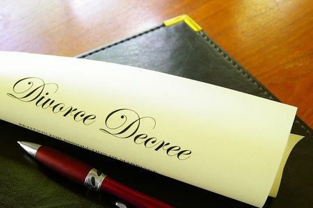Closeup of a divorce decree, rolled up with pen photo