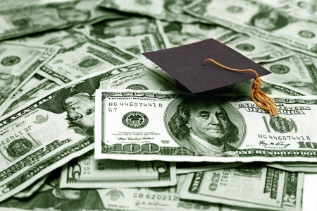 education loan: small graduation cap and money -- educational cost concept Stock Photo