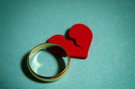 damaged: wedding ring and broken red heart - divorce concept