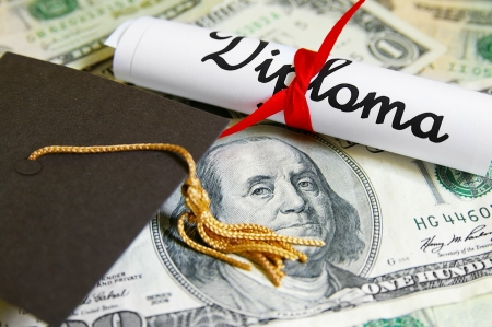 closeup of a mini graduation cap and diploma on money photo