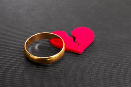 separation: gold wedding ring and red broken heart   divorce concept   Stock Photo