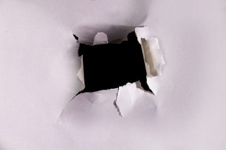 torn hole in a piece of textured paper Stock Photo - 14033982