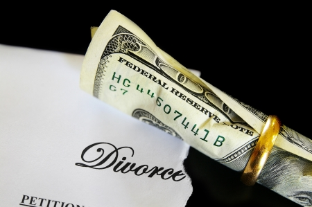 Divorce decree and rolled up cash in a wedding ring photo