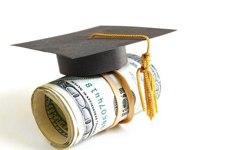 onderwijs: mini graduation cap op een rol van geld Stockfoto
