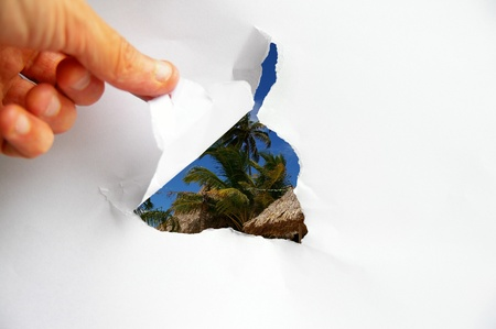 revealed: tropical resort revealed behind torn paper Stock Photo