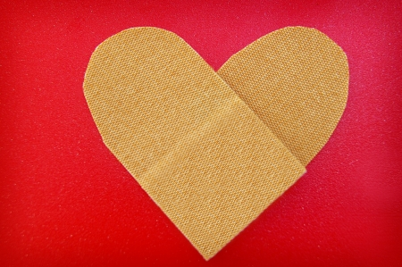 bandage in a heart shape, on red textured background photo