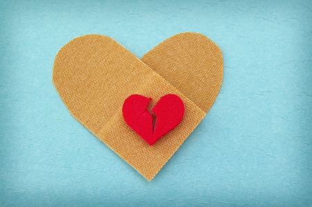 broken red heart on a heart shaped bandage Stock Photo