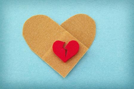 gebroken rood hart op een hartvormige bandage