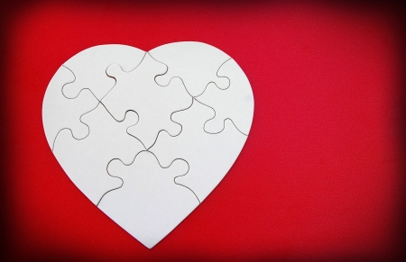 solves: white puzzle shaped heart on red background